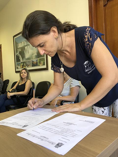 Presidente do SINPREFI, Marli M. Queiroz assina notificação sobre data da reunião. (Foto Assessoria)